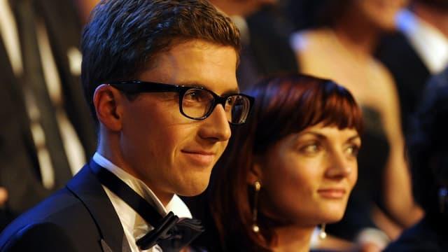 Simon Ammann im Anzug mit Fliege posiert zusammen mit seiner Frau.