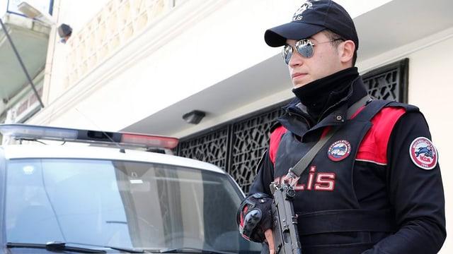 Türkischer Polizist mit Maschinenpistole steht Wache vor einem Haus, hinter ihm ein Polizeifahrzeug