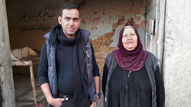 Mann und Frau vor kaputtem Gebäude