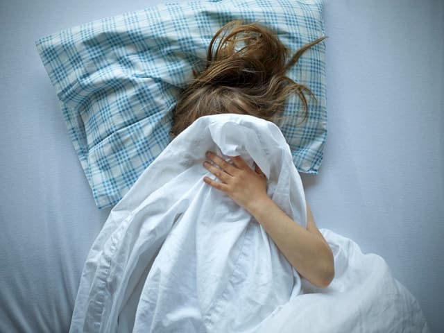 Ein Kind versteckt sich unter der Bettdecke.
