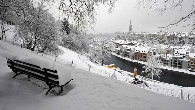 Im Vordergrund steht eine Sitzbank mit etwa 20 Zentimeter Schnee darauf. Die Bank schaut Richtung Bildhintergrund. Zu sehen ist eine Fluss und die Stadt mit weissen Dächern.