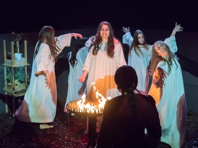 Die Hexen tanzen in weissen Kostümen ums Feuer.