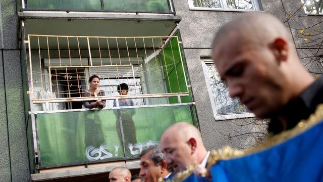 Frau und Kind auf einem Balkon, mehrere Männer schreiten vorbei mit blauem Transparent.