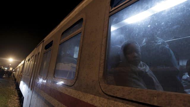Eine Person blickt aus einem Fenster eines Zuges.
