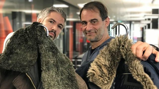 Krispin Zimmermann und Thomy Scherrer halten ihre Winterjacke in die Kamera.