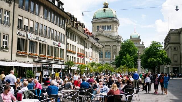 Menschen sitzen in Bern auf dem Bärenplatz in Strassenrestaurants, dahinter das Bundeshaus.