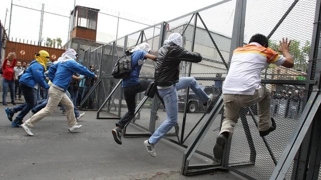 Männer rütteln an einem Zaun