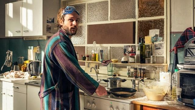 Ein Mann steht mit Bademantel in einer Küche und macht Eierkuchen in einer Bratpfanne.