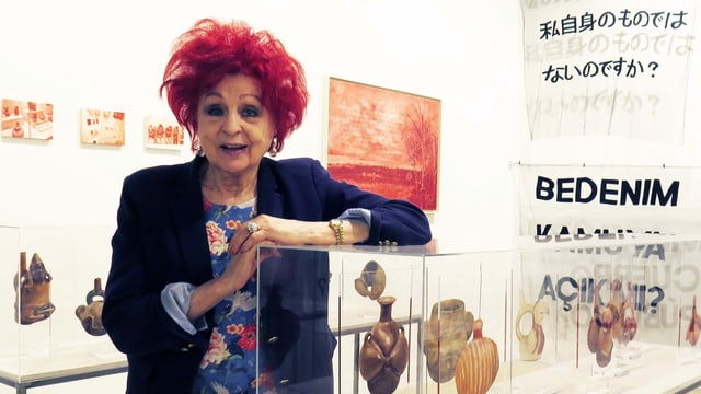 Eine Frau steht in einer Galerie.