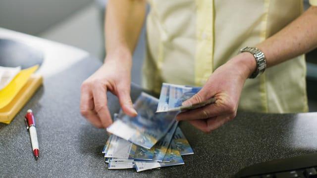 Eine Postangestellte zählt Geld (Symbolbild).