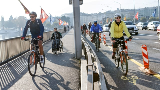 Eine Strasse und ein Trottoir in Zürich. Auf beiden fahren Velofahrer.