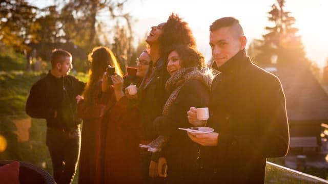 Sechs junge Menschen in Winterbekleidung werden von warmen Sonnenstrahlen beleuchtet.