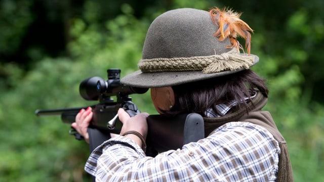 Eine Frau mit grünem Filzhut hält ein Gewehr.