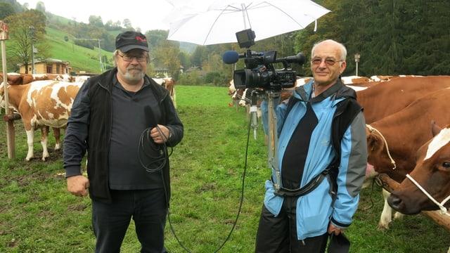 Alfred von Niederhäusern und Karl Schönenberger stehen auf einer Wiese mit Kühen im Hintergrund