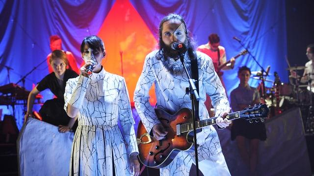 Basler Band «The bianca Story» in weissen Kostümen vor bunt geleuchtetem Hintergrund.