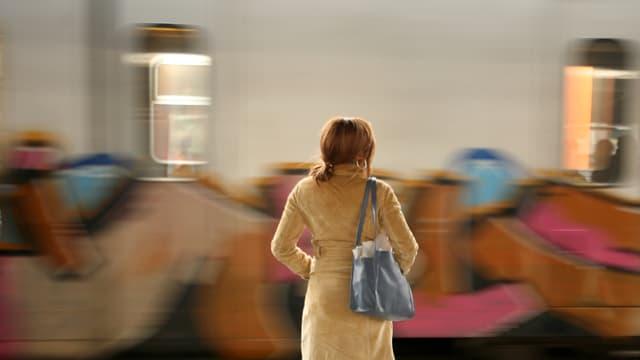 Ein Frau steht am Bahnsteig und schaut auf einen vorbeifahrenden Zug.