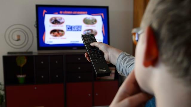 Junge mit Fernbedienung in der Hand sitzt vor dem Fernseher
