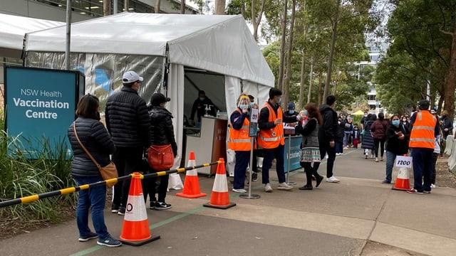 Menschen warten vor einem Impfzentrum.