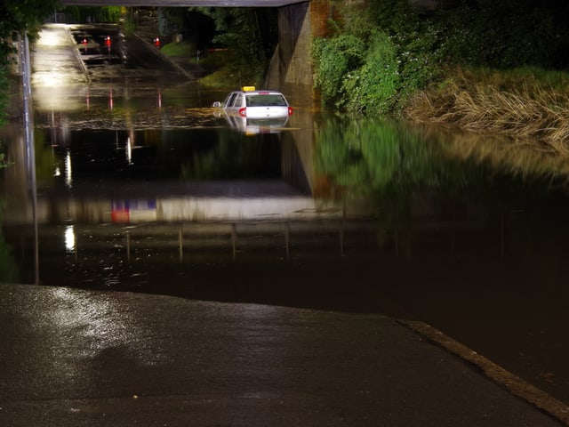 Ein Taxi geht auf einer überschwemmten Strasse in Chur baden. (Stadtpolizei Chur)