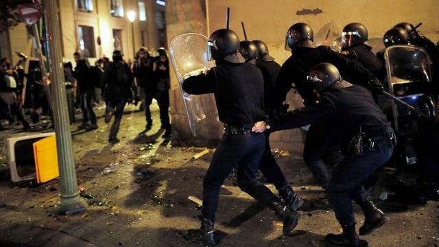 Polizisten und Demonstranten kämpfen gegeneinander.