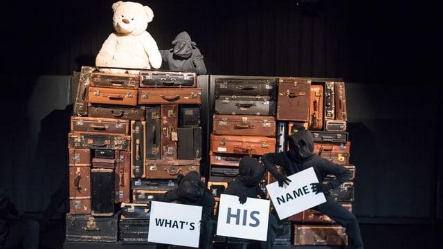 Eine Wand mit Koffern - oben sitzt der Plüsch-Paddington-Bär. Unter sind Tänzer mit Plakaten, auf ihnen steht: What's his name?