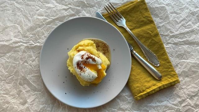 Ein Teller mit Kartoffelstock mit pochiertem Ei und brauner Butter.