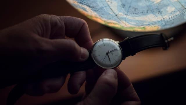 Ein Mann stellt seine Armbanduhr ein.