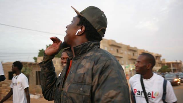 Ein schwarze Mann mit Mütze und Airpods, neben ihm zwei Mäbber in weissen Shirts.