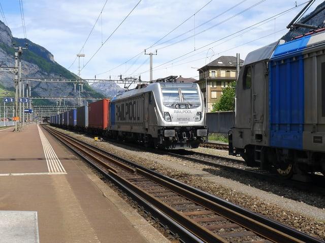 Eine zweite Lokomotive dockt sich vorne an den Güterzug an.