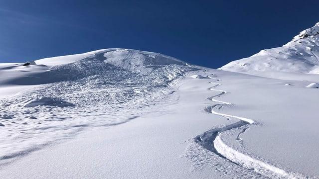 Neuschnee mit einer Skispur.