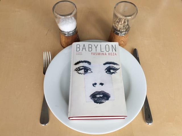 Der Roman «Babylon» von Yasmina Reza liegt auf einem weissen Teller, Messer und Gabel daneben. Oberhalb steht eine Pfeffer- und Salzmühle