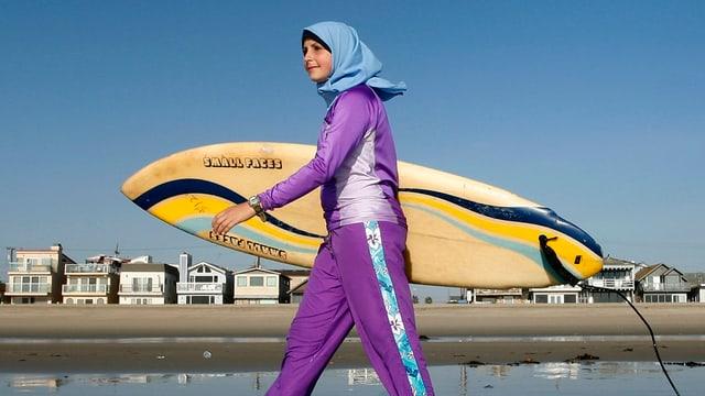 Muslima spaziert in einem violett-blauen Burkini am Strand von Newport in Kalifornien, der Anzug bedeckt ihren ganzen Körper, mit Ausnahme der Füsse, Hände und des Gesichts.