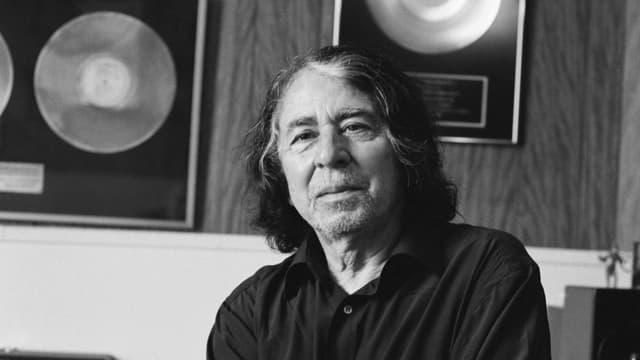 Schwarzweissbild: EIn älterer Mann mit langen Haaren vor zwei gerahmten goldenen Schallplatten.