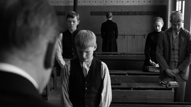 Drei Schüler und eine Schülerin stehen mit gesenkten Köpfen hinter ihren Pulten. Vorne im Bild ist der Kopf des älteren Lehrers von hinten zu sehen.