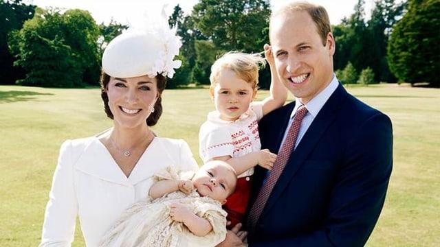 Prinz William und Kate mit ihren beiden Kindern auf einer Wiese.
