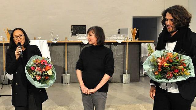 Zwei Frauen und ein Mann, stehend, zwei von ihnen mit Blumenstrauss. Eine Frau spricht in ein Mikrofon.