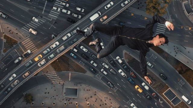 Die Ansicht eines Strassennetzes von sehr weit oben. Viele Strassen, Autos stauen sich. Weit oben schwebt ein junger Mann.
