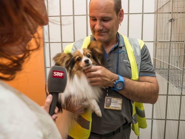 SRF-Autorin mit Mikrofon vor Mann mit Hund auf dem Arm