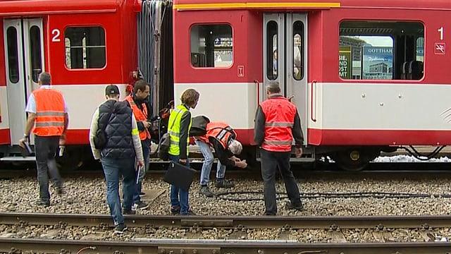 Fachleute auf dem Bahntrasse schauen sich den Zug an.