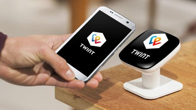Jemand hält ein Smartphone mit Twint-App an einen Twint-Beacon.