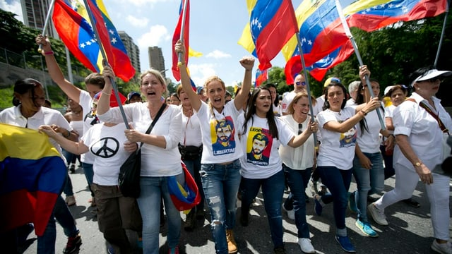 Frauen demonstrieren mit venezolanischen Flaggen.