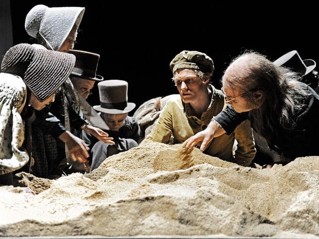 Mehrere kleinwüchsige, altmodisch gekleidete Schauspieler umringen den Sandhaufen mir Jirka Zett.