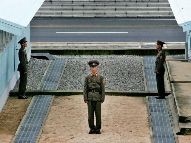 Drei schmächtige, nordkoreanische Soldaten an der Demarkationslinie