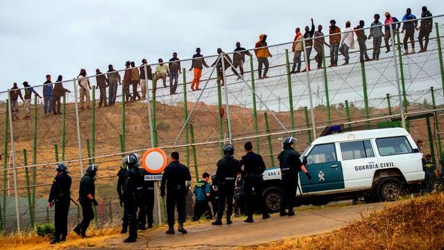 Die Guarda Civil warten unten, die Flüchtlinge sind oben auf dem Zaun.