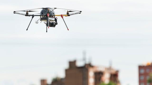Eine Drohne fliegt in der Luft, im Hintergrund ein Wohnblock.