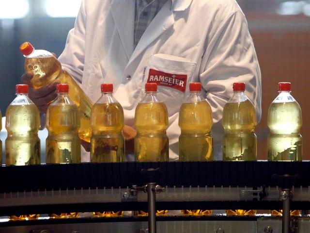 Eine Person überprüft eine Flasche Ramseier Apfelsaft.