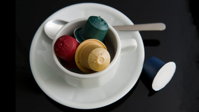 verschiedene Kaffeekapseln in einer Espressotasse.