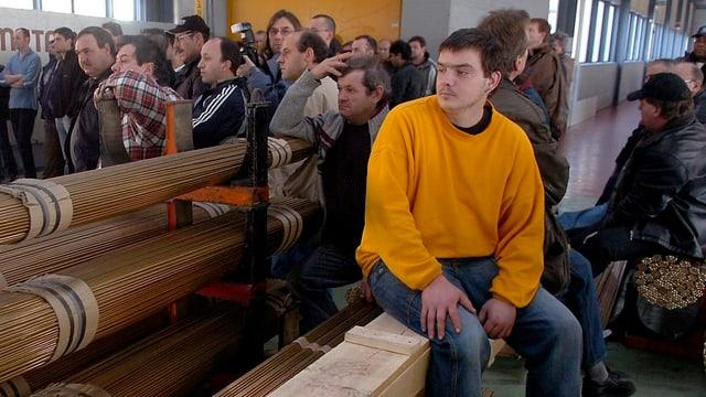 Arbeiter sind in einer Fabrikhalle zu einer Orientierung versammelt.
