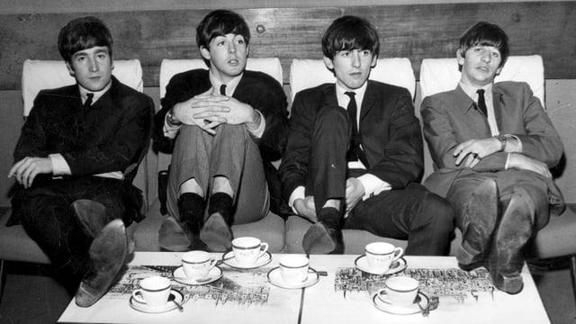Vier Männer sitzen auf einem Sofa und haben Teetassen vor sich.