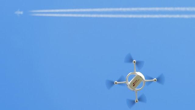 Flugdrohne am Himmel, weit darüber ein Flugzeug mit Kondensstreifen.